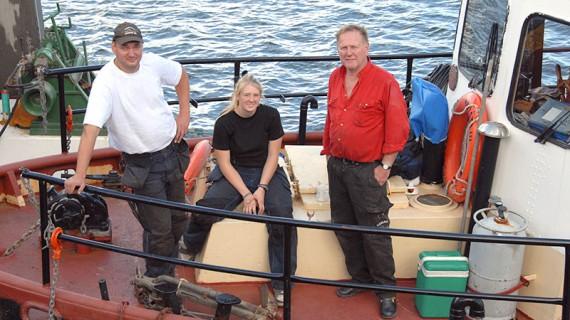 Trion på bogserbåten. Sven Olsson, till höger, har i många år arbetat med ved- och timmertransporter från skärgården. Just idag tillsammans med sin anställde Roger Pettersson och sjömanspraktikanten Linnea Gustafsson.
