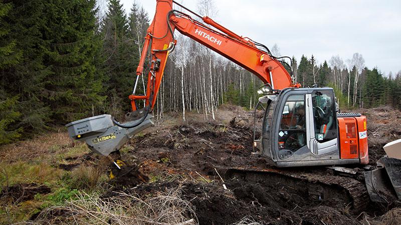 Grävaren tar sig fram med god bärighet på hygget och utför planteringsjobbet.