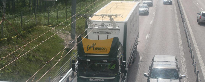 Kraften förs över från ledningar i luften genom en strömavtagare, pantograf, på lastbilens tak.